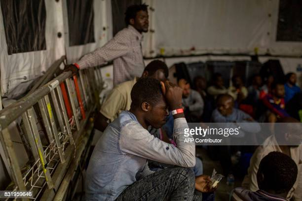 A migrant rests on the deck of the Aquarius rescue ship run by NGO SOS Mediterranee and Medecins Sans Frontieres after his transfer from the NGO...