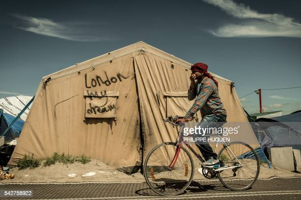 TOPSHOT A migrant rides his bicycle inside the 'Jungle' camp for migrants and refugees in Calais on June 24 the day after Britain voted to leave the...