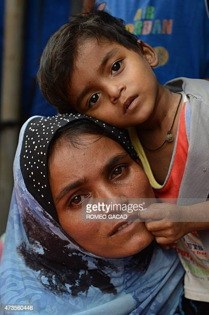 A migrant Rohingya woman from Myanmar with her child waits for aid at the new confinement area in the fishing town of Kuala Langsa in Aceh province...