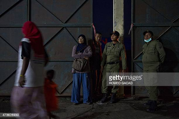 A migrant Rohingya woman with a child prepare in their sleeping quarters at a warehouse guarded by local civil security personnel and volunteers at...