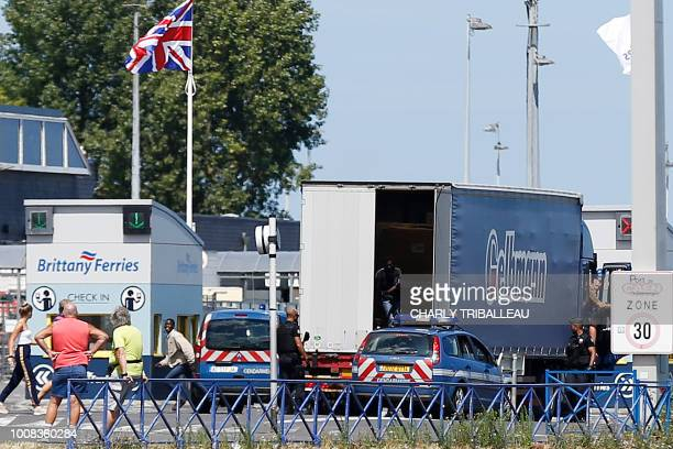 A migrant runs as another peers out of the back of a lorry after police stopped the the truck at the Brittany ferry port in Ouistreham northwestern...