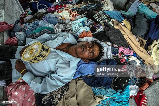 A migrant seen sleeping at a temporary shelter on May 17 2015 in Kuala Langsa Indonesia Hundreds of migrants from Myanmar and Bangladesh have taken...