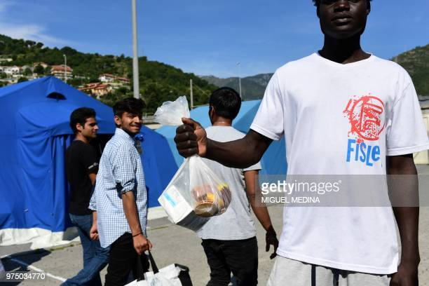 A migrant shows his bag of food as other migrants pass by at the Italian Red Cross camp in Ventimiglia northern Italy on June 15 2018
