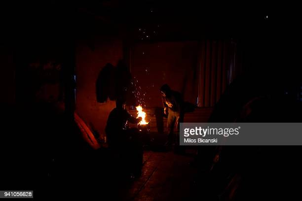Migrant sit next to fire at the disused factory where migrants and refugees are living in poor conditions with no running water and toilets near the...