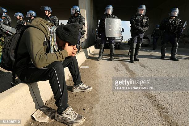 """Migrant sits as French gendarmes stand guard at the """"Jungle"""" migrant camp in Calais, northern France, on October 26 during a massive operation to..."""