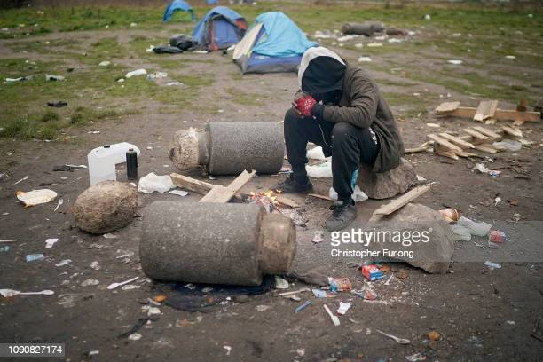 Migrant sits by his camp fire in an area near Calais Port known as 'The Jungle' on January 07, 2019 in Calais, France. In recent weeks there has been...