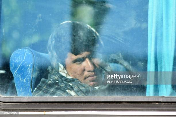 A migrant sits in a bus after the evacuation of a makeshift camp in a park across the City Hall in Sarajevo on May 18 in order to relocate them in...