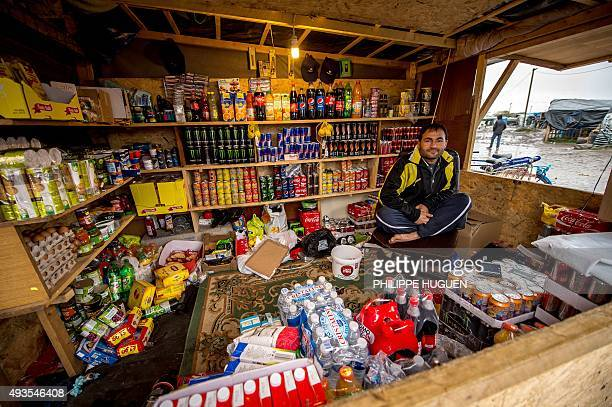 A migrant sits in a makeshift shop in the encampment where thousands of migrants live in the hope of crossing the Channel to Britain known as the...