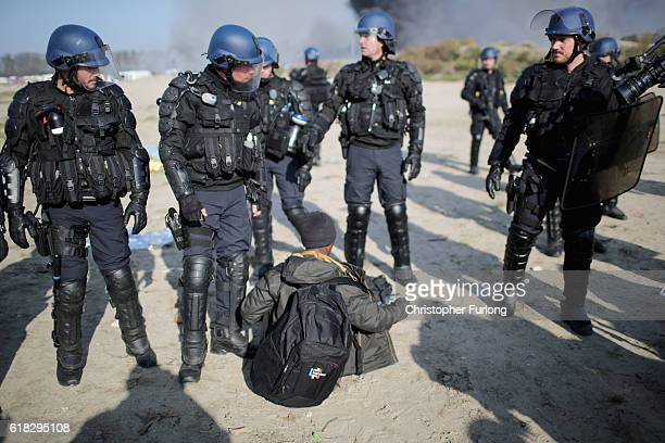 A migrant sits in front of riot police as they clear the notorius Jungle camp as authorities demolish the site on October 26 2016 in Calais France...