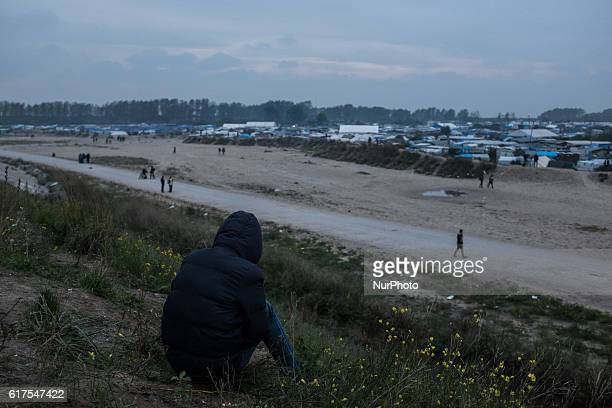 A Migrant sits in the Calais Jungle in Calais France on an embankment an looks in the direction if the camp on 23 October 2016 The refugee camp on...