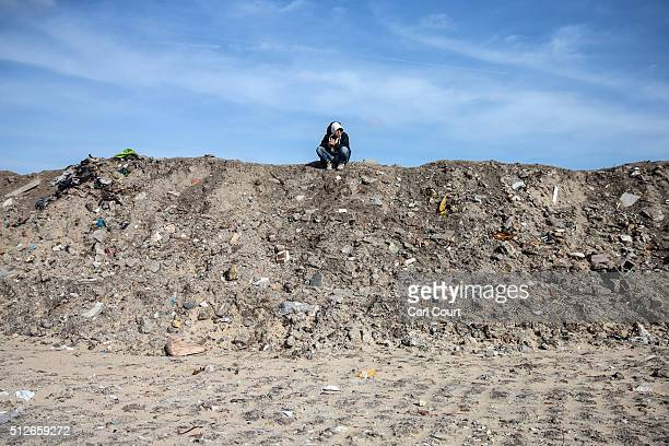 A migrant sits on a mound in a cleared area that used to be part of the 'jungle' camp on February 27 2016 in Calais France The French authorities...