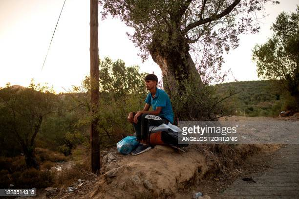 Migrant sits on his belongings near the burnt Moria refugee camp on the Greek island of Lesbos on September 14, 2020. - Over 11,000 people --...