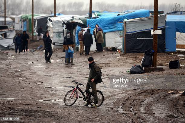 A migrant sits on his bike near cleared land in the 'jungle' migrant camp on March 01 2016 in Calais France Police and demolition teams are...