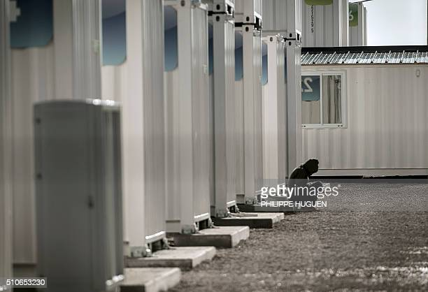TOPSHOT A migrant sits outside a housing container in the 'Jungle' camp in the port town of Calais northern France on February 16 2016 Local French...