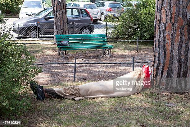 A migrant sleeps in the park near the Red Cross unit on June 18 2015 in Gorizia Italy Approximately 50 migrants enter Italy through the eastern part...