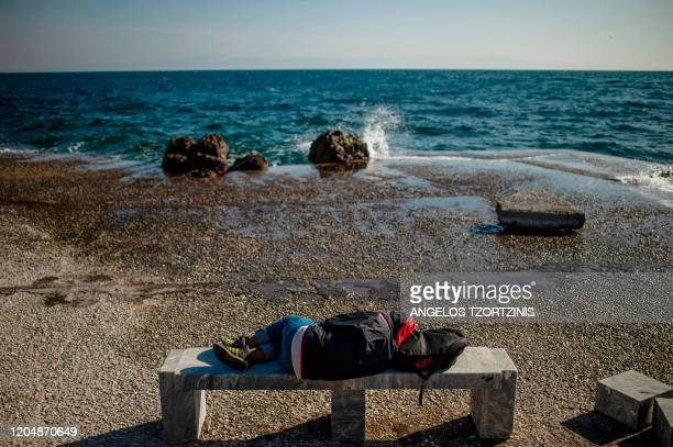 TOPSHOT A migrant sleeps on a bench at the harbor quay on the island of Lesbos Greece on March 3 2020 Greece was on a state of alert on March 1 2020...