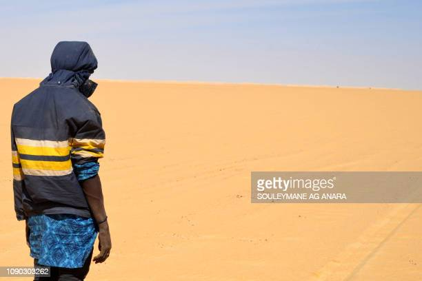 A migrant stand in the desert as he and others mainly from Niger and Nigeria make their way across the Air desert in northern Niger towards the...