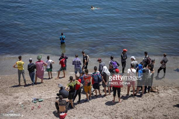 Migrant stand on the beach waiting to cross from the northern town of Fnideq across the border from Morocco to Spain's North African enclave of Ceuta...