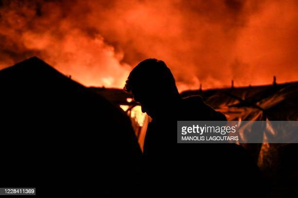 Migrant stands near tents as a fire burns in the Moria camp on the island of Lesbos on September 9, 2020. - The migrant camp of Moria, on the Greek...