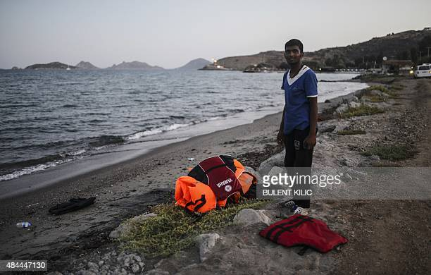 A migrant stands next to abandoned life jackets early on August 19 on the shore of Bodrum southwestern Turkey The UN refugee agency said in the last...
