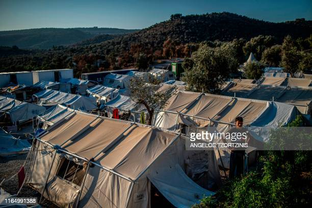 TOPSHOT A migrant stands outside amid tents at the official refugee camp of Moria on the Greek island of Lesbos on August 31 2019 On August 29...