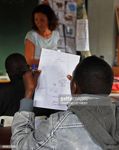 A migrant student looks at a map of the 'New Jungle' migrant camp drawn by speech therapist Virginie Tiberghien as she gives a French class to...