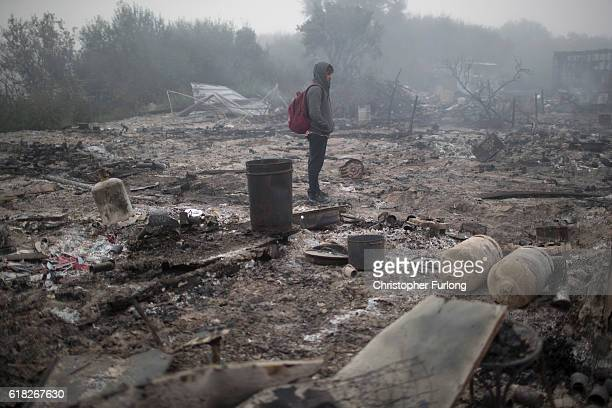 A migrant surveys the smouldering remains of shacks and makeshift shops in the notorious Jungle camp after migrants set fire to them last night on...