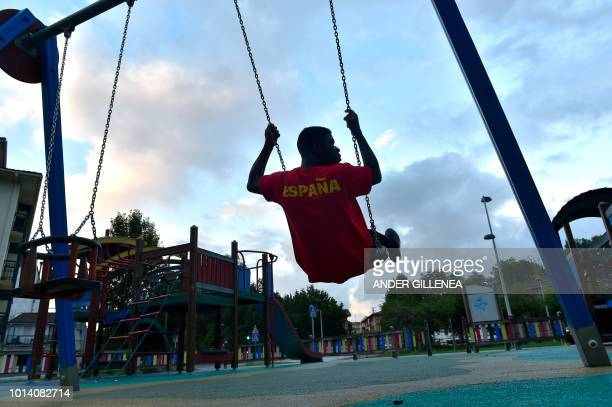 A migrant swings outside the migrants reception center in the Spanish Basque city of Irun on August 9 2018 With migrant arrivals to Spain's southern...