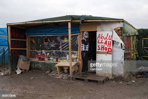 A migrant talks on his phone outside a shop in the camp known as 'The Jungle' on January 5 2016 in Calais France Thousands of migrants continue to...