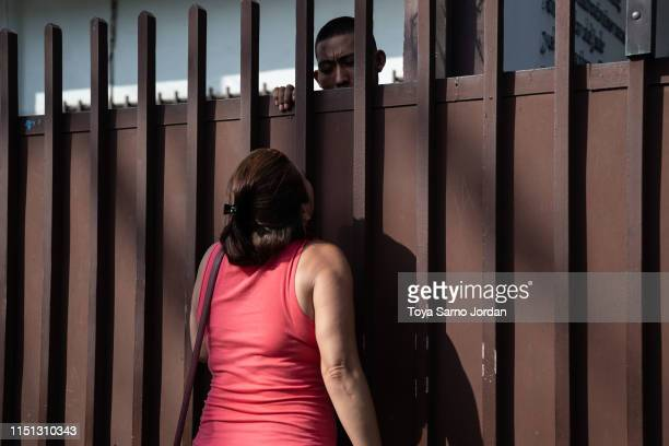 A migrant talks to a family member through a fence at the Mexican Commission for Refugee Assistance on June 21 2019 in Tapachula Mexico Hundreds of...