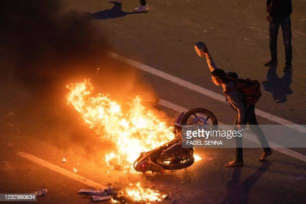 Migrant throws a rock onto a burning motorbike as they clash with Moroccan riot police in protest at being stopped from crossing the border, in the...