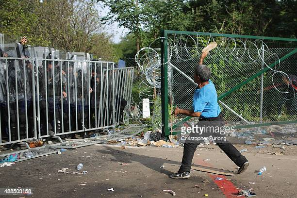 A migrant throws a shoe at Hungarian riot police as an attempt is made to break the border post gate and pull down the razor wire fence on September...