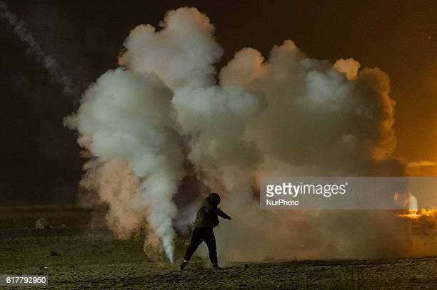 A Migrant throws in the Calais Jungle during small clashes a tear gas grenade in the direction of the police in Calais France on 2016 The refugee...