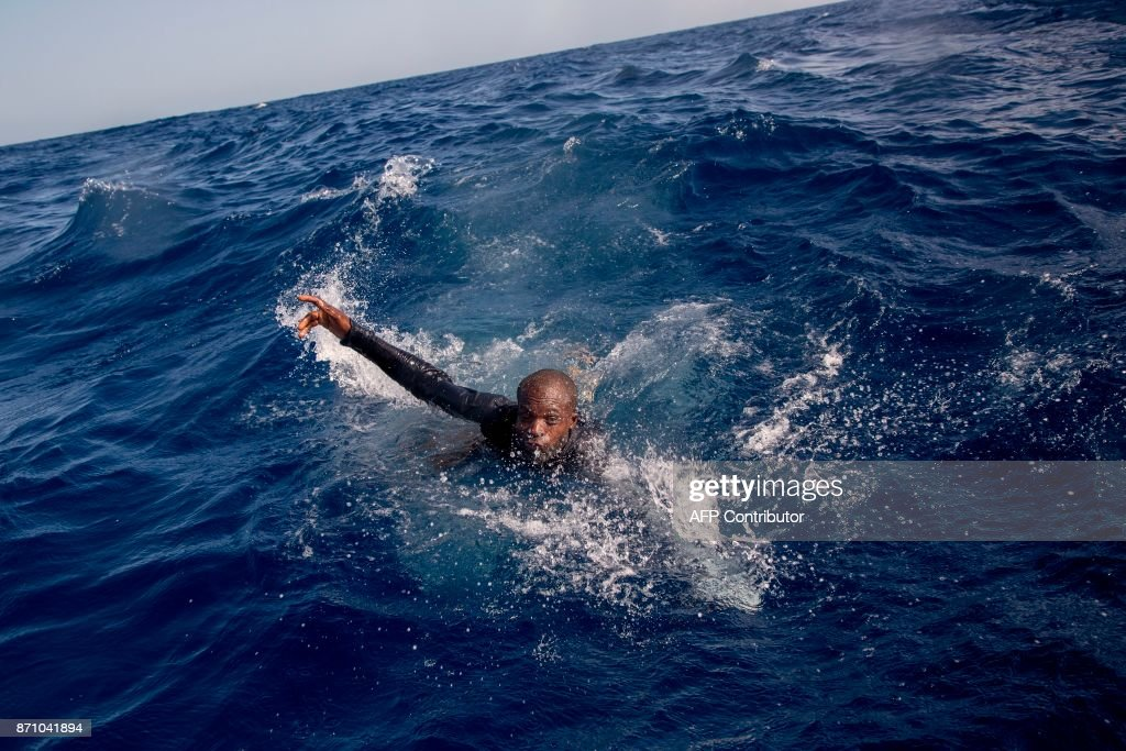 A migrant tries to board a boat of the German NGO Sea-Watch in the Mediterranean Sea on November 6, 2017. During a shipwreck, five people died, including a newborn child. According to the German NGO Sea-Watch, which has saved 58 migrants, the violent behavior of the Libyan coast guard caused the death of five persons. PHOTO / Alessio Paduano