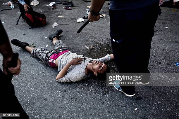 A migrant tries to recover after clashes with the police during a protest at the Lesvos Port on September 6 as migrants demand to be transferred...