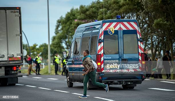 A migrant trying to reach the Channel Tunnel runs past a police car in Coquelles near Calais northern France on late July 29 2015 One man died...