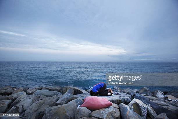A migrant waits at the French border hoping to enter the country on June 16 2015 in Ventimiglia Italy Some 200 migrants from Africa have been blocked...