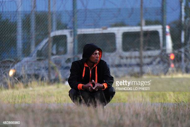 A migrant waits in Coquelles near the northern French port of Calais on August 3 2015 Migrants in Calais made around 1700 attempts overnight to...