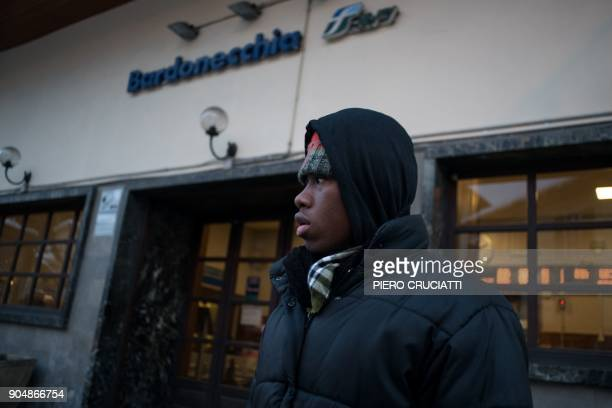 A migrant waits in front of Bardonecchia station in Bardonecchia on January 14 2018 Migrants are now trying to reach France crossing the Italian Alps...