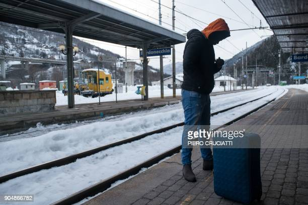 A migrant waits on the platform of Bardonecchia station in Bardonecchia on January 14 2018 Migrants are now trying to reach France crossing the...
