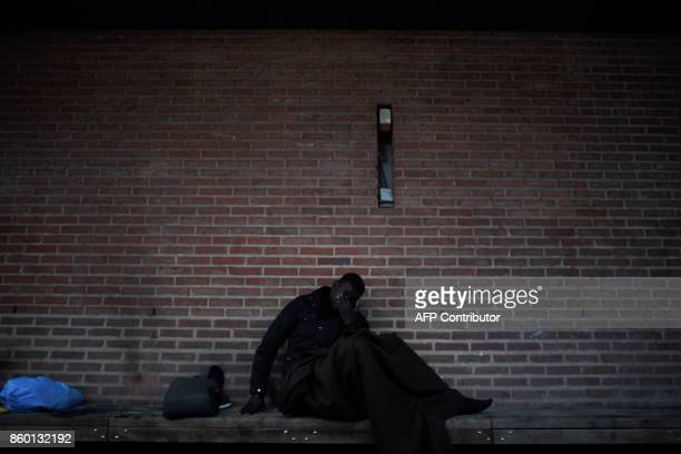 A migrant wakes up after sleeping on the floor in SaintDenis outside Paris on October 11 2017 Unprecedented waves of migration are affecting the...