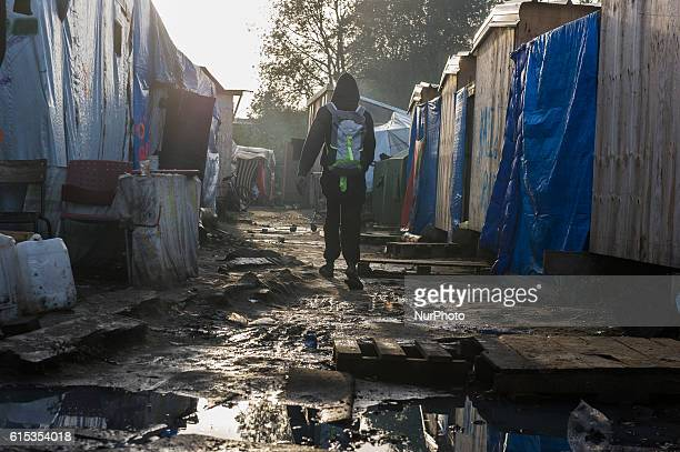 A Migrant walk in the Calais Jungle on a path between the huts in Calais France on 17 October 2016 The refugee camp on the coast to the English...