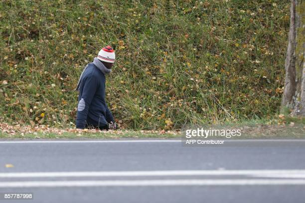 A migrant walks along a road in Ouistreham near Caen northwestern France on October 5 2017 Migration is a hot button issue in Europe and politicians...