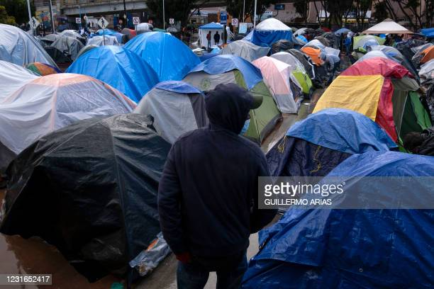 Migrant walks amid tents at an improvised camp outside El Chaparral crossing port as he and others wait for US authorities to allow them to start...