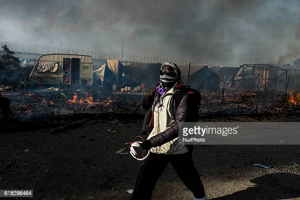 A migrant walks between burned down huts in the Calais Jungle on October 26 2016 Huge fires destroyed a mayor part of the refugee camp today