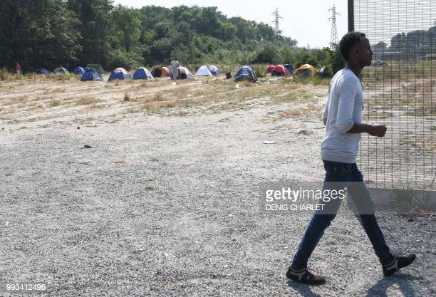 A migrant walks by tents in Calais on July 7 2018 Several hundred people took part in a 'solidarity' march in support of migrants in Calais organised...