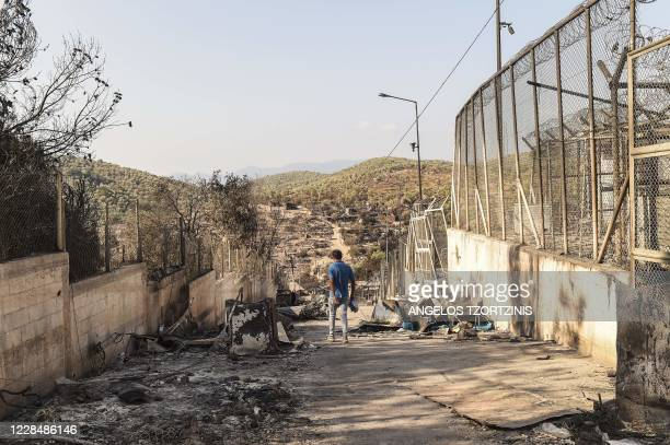 Migrant walks in the burnt camp of Moria on the island of Lesbos, a few days after a fire destroyed the Moria refugee camp, on September 13, 2020. -...