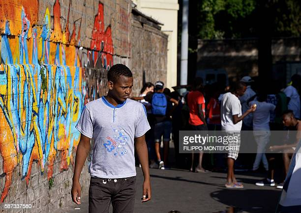 A migrant walks in the street of Via Cupa outside the former Baobab migrants reception centre next to the Tiburtina train station in Rome on August 8...