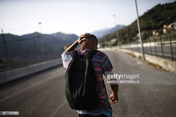 A migrant walks next to the Roya River on August 8 2017 in Ventimiglia close to the French border / AFP PHOTO / Marco BERTORELLO