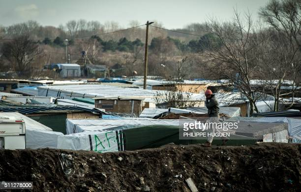 TOPSHOT A migrant walks on a embankment of earth surrounding the 'jungle' migrants and refugee camp on February 19 2016 in Calais northern France /...